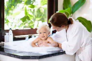 Mother washing baby in bubble bath. Water fun.