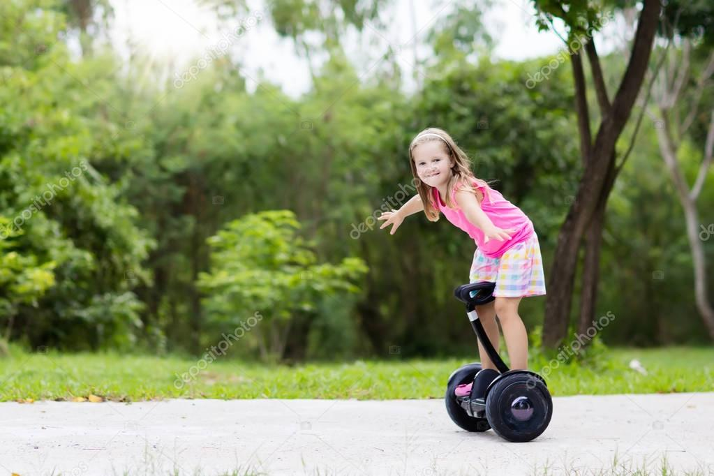 Child on hover board. Kids riding scooter
