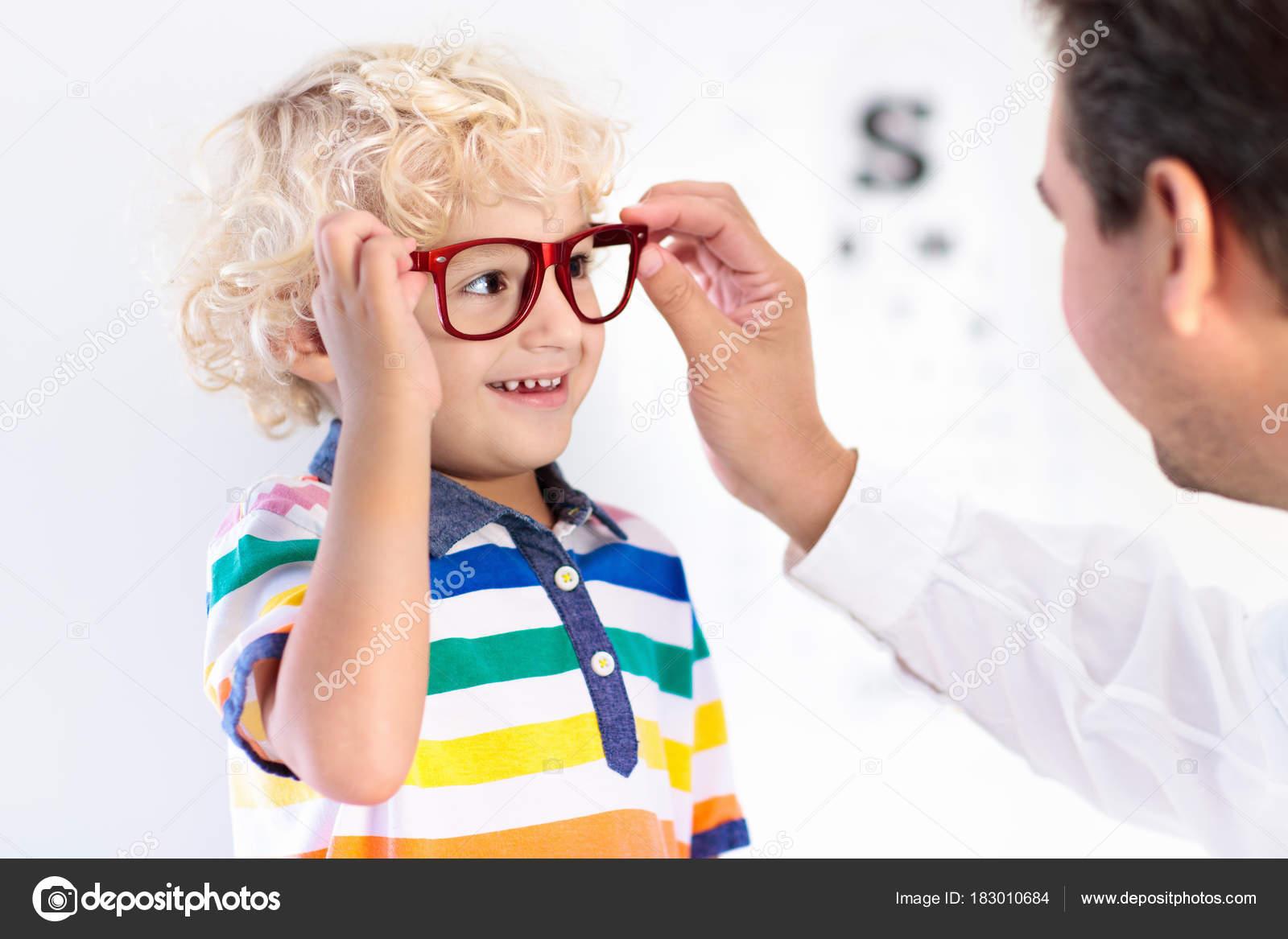 38479aa717 Child at eye sight test. Little kid selecting glasses at optician store. Eyesight  measurement for school kids. Eye wear for children.