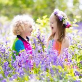 Fotografie Kids with bluebell flowers, garden tools