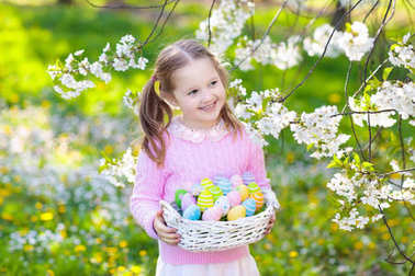 Child with bunny ears on garden Easter egg hunt