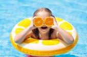 Fotografie Child in swimming pool. Kid eating orange.