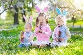Fotografie Garten-Ostern-Eiersuchen. Kinder essen Schokolade Hase