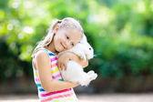 Fotografie Kind mit Kaninchen. Osterhase. Kinder und Haustiere