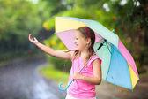 Fotografie Kind mit Regenschirm im Sommerregen spielen