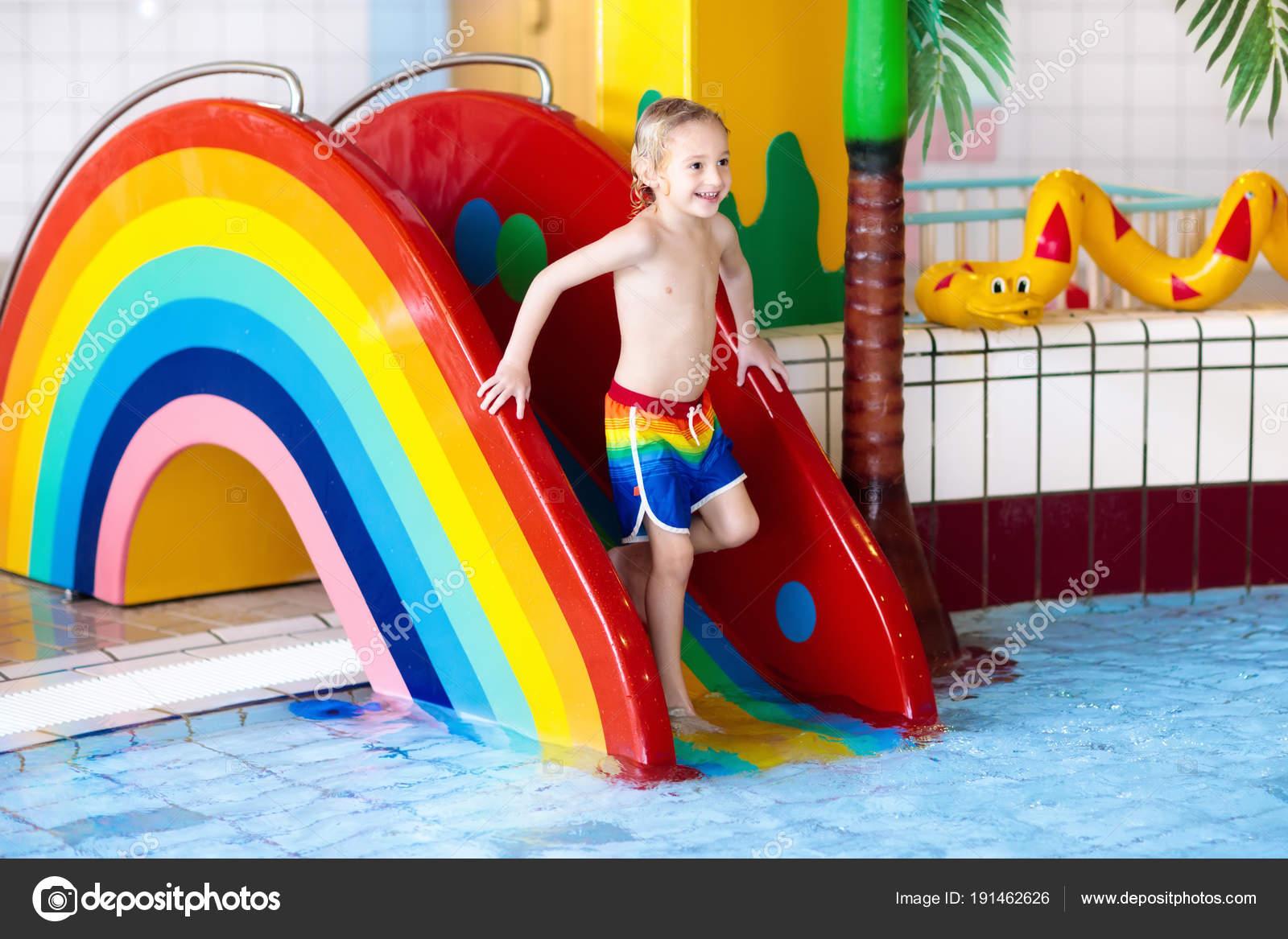 Child On Swimming Pool Slide Kid Having Fun Sliding In Water Amusement Park Kids Swim Family Summer Vacation Tropical Resort