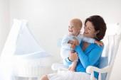 Junge Mutter hält ihr neugeborenes Kind. Mama Pflege Baby. Frau und Neugeborene Junge im weißen Schlafzimmer mit Schaukelstuhl und blau Krippe. Kindergarten-Innenraum. Mutter mit Kind lachen spielen. Familie zu Hause