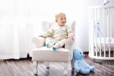 Baby boy in bedroom. Infant child sitting in white chair at round wooden bed. Kids room interior. Children fashion and sleep wear. Kid at nursery crib. Toys for toddler. Knitting for kids.