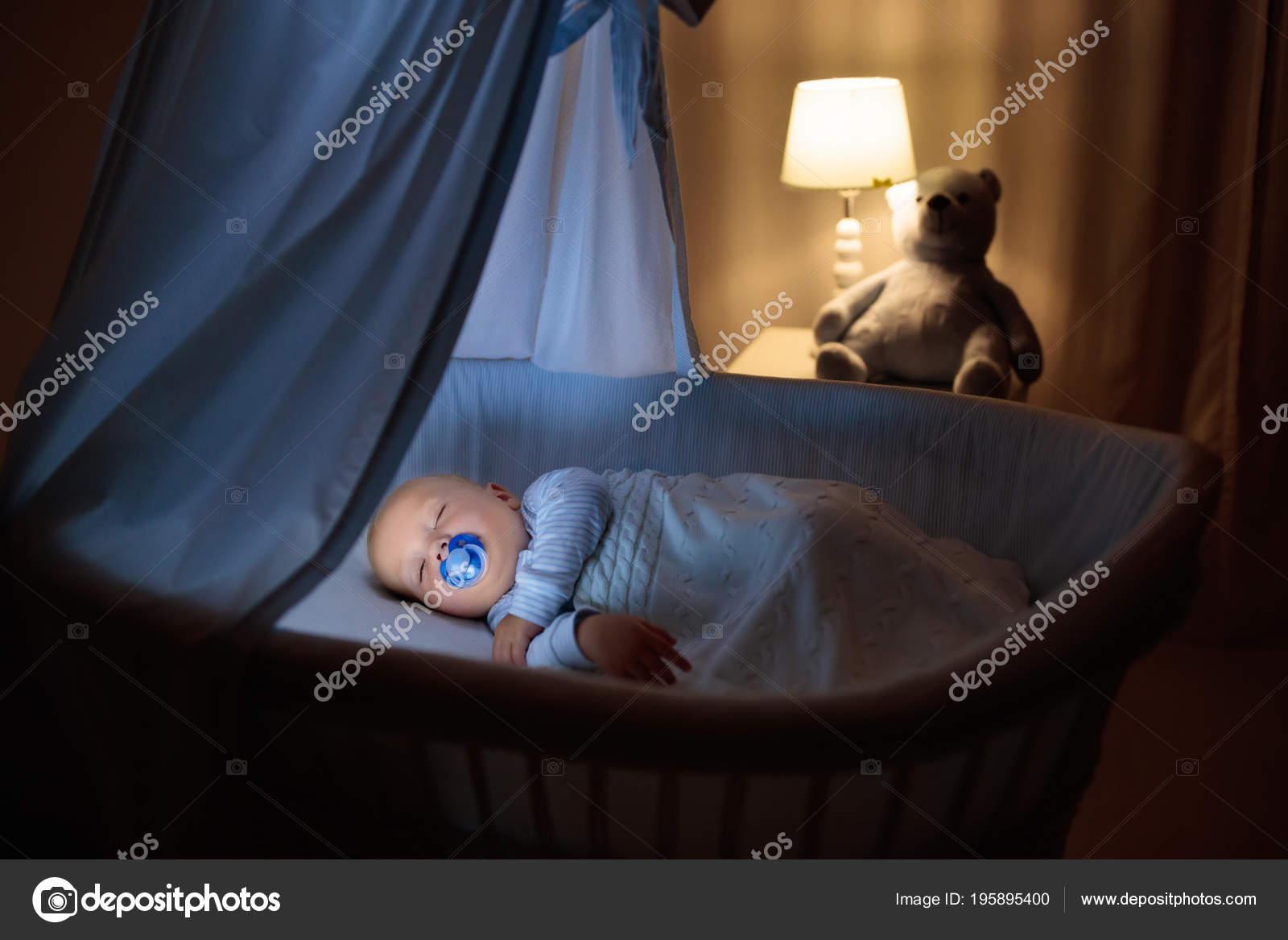 Entzückende baby mit schnuller schlafen der nacht blau stubenwagen