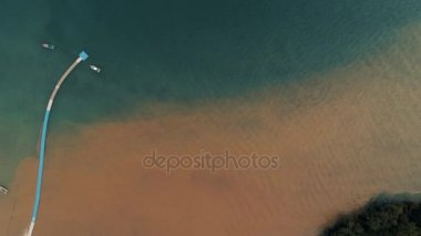 Thailand Coral Island Drone Shot Water dyed in the color of sand after tropical rain mingles with the clear water of the Adaman Sea