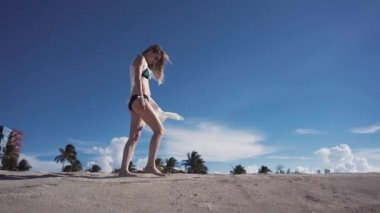 Girl, beach, sea, wind in your hair, girl in bikini walking along the beach with sand
