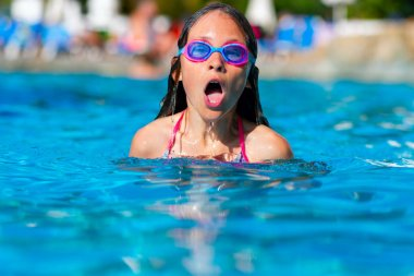 Young girl swims freestyle in the pool in glasses. Teenager inhales deeply above the surface of the water.