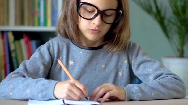 Egy nagy fekete szemüveges lány ír egy füzetbe. Sárga toll a jobb kézben. Közelkép.