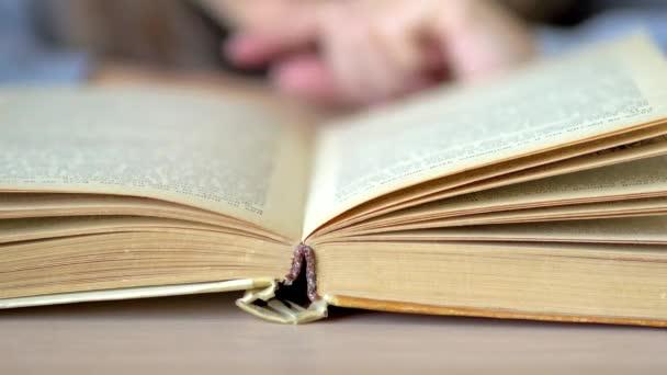 Otoč list v knize ležící na stole. Zavřít pohled.