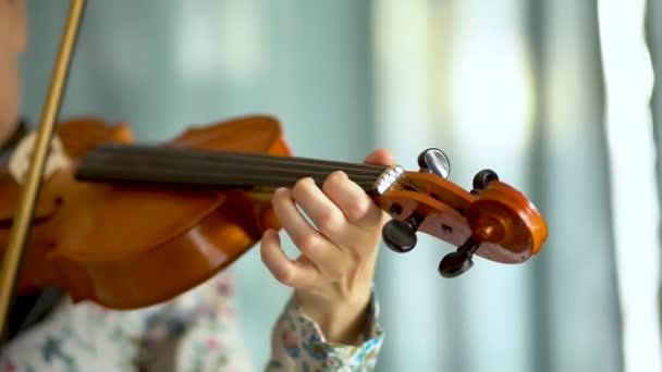 Fiatal nő hegedül. Egy női hegedűs keze egy hegedű fogólapján. Közelkép