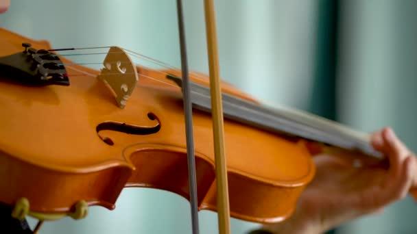 Hegedű és meghajlás egy fiatal hegedűművész kezében. Közelkép