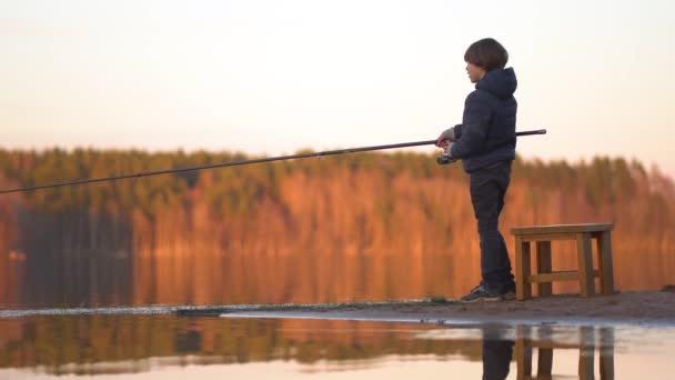 A kisfiú napnyugtakor horgászik a tavon.