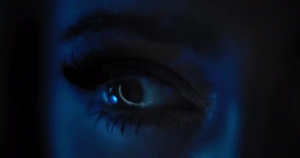 Nahaufnahme eines Frauenauges mit wunderschönem Party-Make-up, langen schwarzen Wimpern, die sich in einem dunkelblauen Licht öffnen. Zeitlupe, dunkles Studiolicht. bmpcc 4k