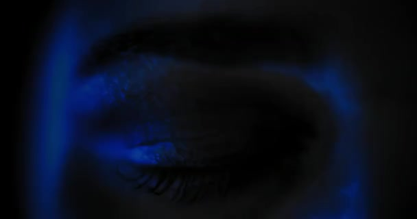 Close up of a womans eye with beautiful make up, opening in a dark blue lighting. Slow motion, dark studio light. BMPCC 4K