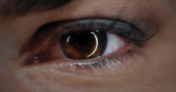 Close up of a womans eye with beautiful make up, opening in a studio lighting. Slow motion. BMPCC 4K