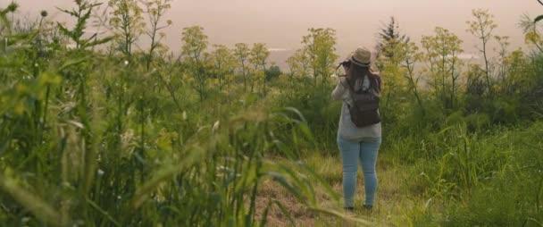 Ein junges Mädchen mit Rucksack und Hut geht durch die grüne Wiese und fotografiert Landschaft und Natur bei Sonnenuntergang. SLOW MOTION, SHALLOW DOF. Abenteuer, Lifestyle-Konzept. BMPCC 4K