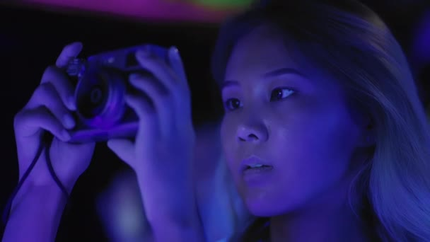 Young Asian girl shooting photo or video at party in club or shopping center