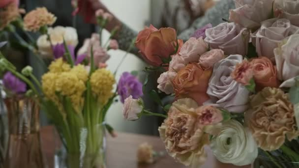 florist at work in flower shop creates big fresh bouquet of roses and carnations