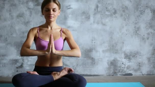 Krásná mladá dívka dělá jógu doma.