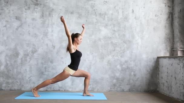 Žena cvičí jógu doma na modrá mat. Wellness koncept