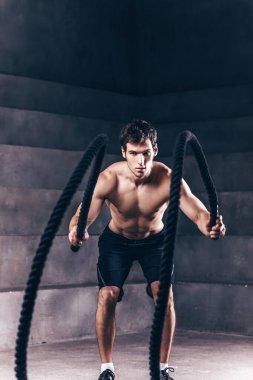 Muscular powerful man training with rope. Bodybuilder in dark studio.