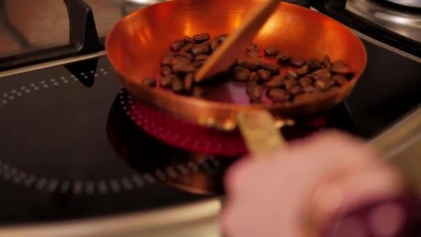 Dívka míchat kávová zrna s stěrkou v měděné pánvi