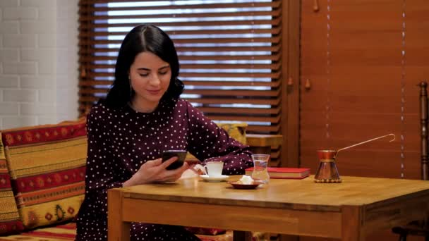 Young girl in polka dot dress drinking coffee