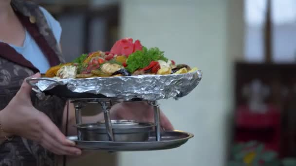 The waiter delivers to the table cooked in a cauldron vegetables.