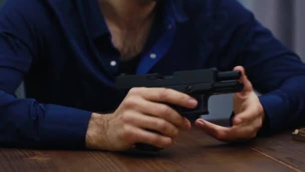 Der Mann, der am Schreibtisch sitzt und eine Waffe in der Hand hält, lädt sie auf, dreht sie in seinen Händen