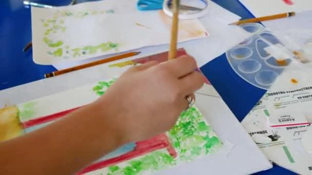 Mädchen lernt mit Aquarellfarben zu malen. zeichnet einen roten Bogen