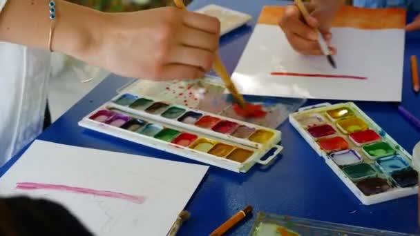 Mädchen lernt mit Aquarellfarben zu malen. mischt Farben