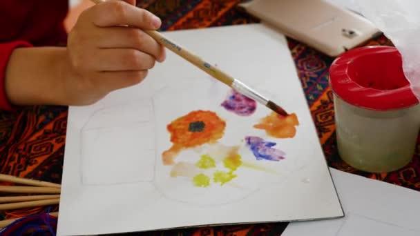 Kleines Mädchen lernt Malen mit Aquarellfarben.