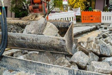 Excavator shovel with granite stones