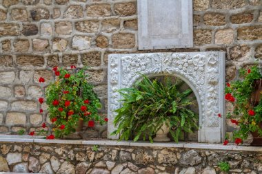 Bas-relief and flowers, courtyard of the Greek Orthodox Wedding Church in Cana, Israel.