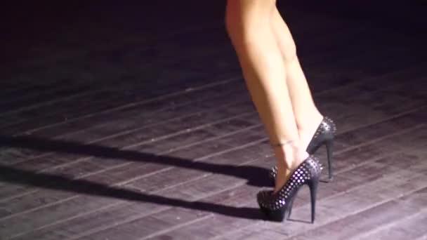 schöne nackte Beine eines jungen Mädchens in einem kurzen Rock mit hohen Absätzen, das zur Musik in einem Nachtclub inmitten der Menge tanzt