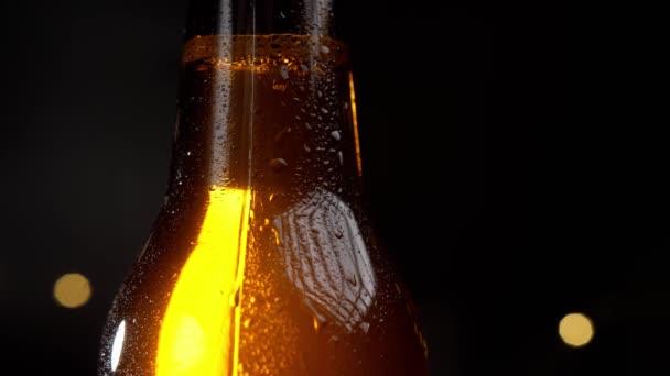 Kapky vody pomalu stékají do studené láhve piva. Na černém pozadí láhev září ve zlatě