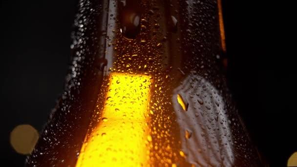 Eine kaltvernebelte Flasche Bier, die mit Tropfen bedeckt ist. Makroaufnahme auf schwarzem Hintergrund. die Flasche leuchtet golden, Tropfen fließen langsam hinunter