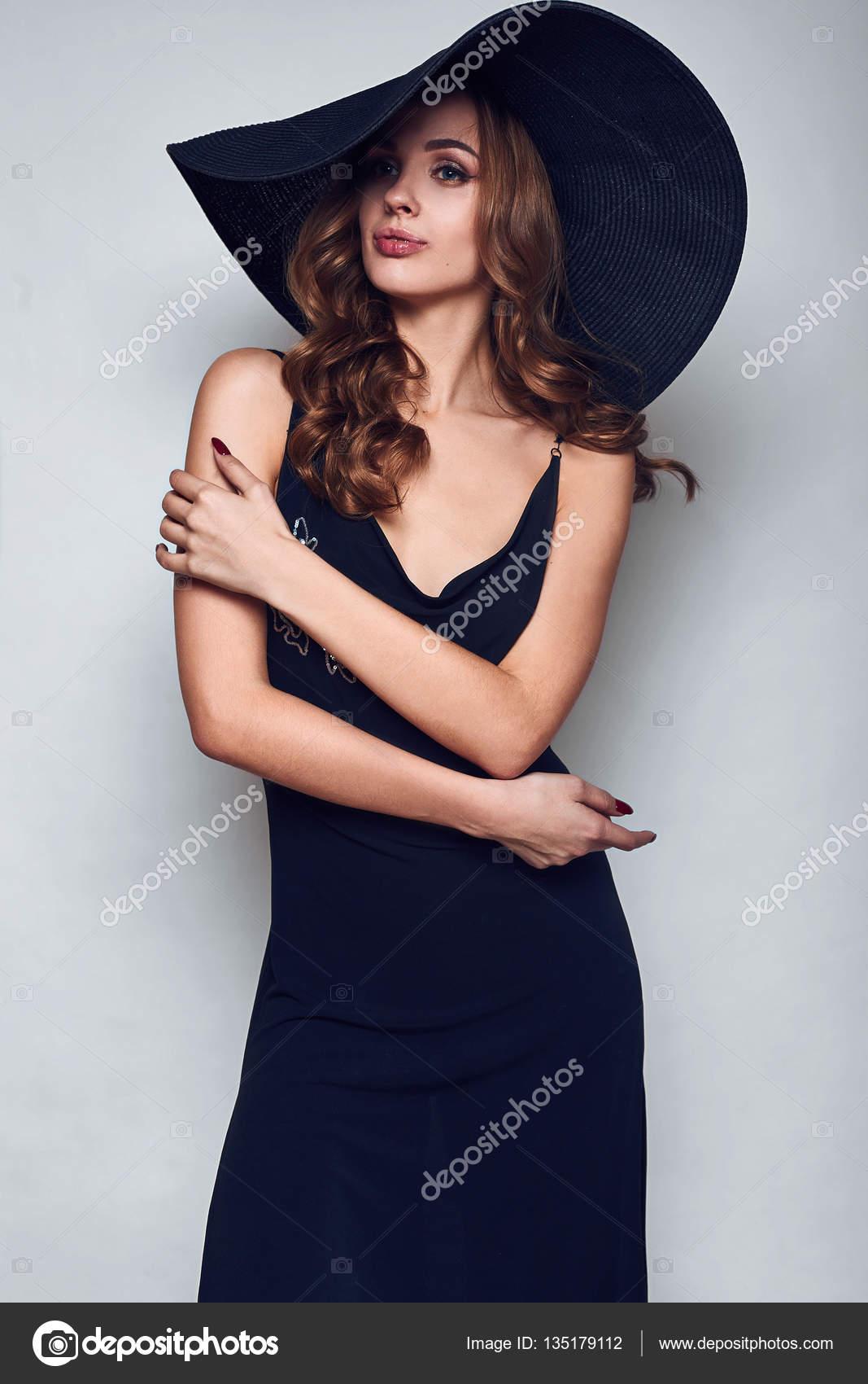 Bella donna elegante in un vestito nero e cappello — Foto Stock ... e782ad7c0707