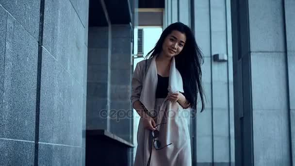 Roztomilý a nádherné Asijské žena v plášti chůzi mezi sloupy