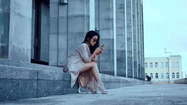 Roztomilé a krásné asijské žena v plášti sedí na schodech