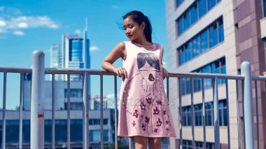 Cute and bright asian woman in fashion dress admiring the city view