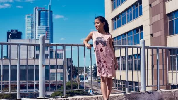 Roztomilý a světlé asijských žena v šatech módní kochat výhledem na moře