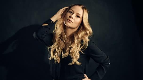 Blondýnka s kudrnatými vlasy pózuje na černém pozadí v studio