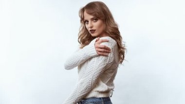 Portrait of sensual positive beautiful blond woman in sweater isolated on white background in studio