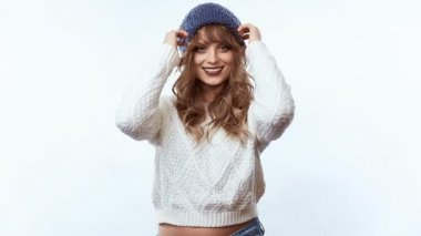 Portrait of sensual positive beautiful blond woman in sweater and blue hat isolated on white background in studio